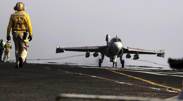 A US warplane lands on the USS George HW Bush aircraft carrier in the Persian Gulf. (AP)