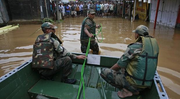 An Indian soldier pulls a boat as flood-hit villagers wait to be rescued (AP)