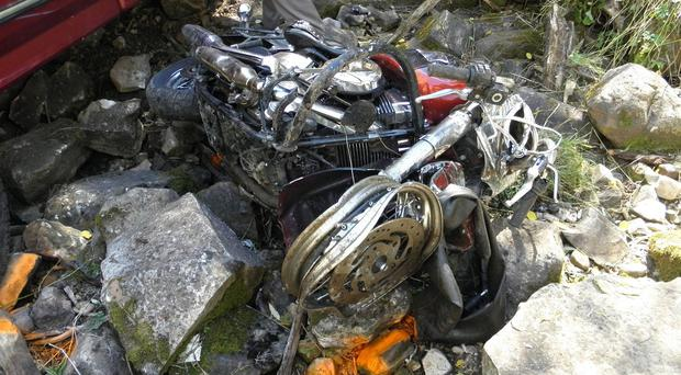 This photo taken on Wednesday, Sept. 24, 2014, and provided by the Utah Highway Patrol, shows an accident where Utah authorities say a motorcyclist from England died after driving on the wrong side of the road in Woodland, Utah. Authorities say the crash happened a little after noon Wednesday east of Woodland in Summit County. Troopers say the man, and another tourist who was also vacationing from England, were driving their motorcycles onto the wrong side of State Route 35 when a truck approached. One of the motorcyclists swerved out of the way, but one was hit. Troopers say both the truck and motorcycle went down a steep, 100-foot embankment. The truck driver was airlifted to the hospital in serious condition. (AP Photo/Utah Highway Patrol)