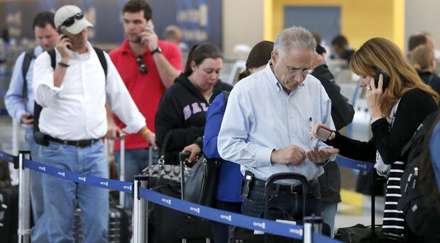 Passengers at O'Hare International Airport can only wait in a United Airlines ticketing queue after a fire in a regional radar centre halted all flights (AP)