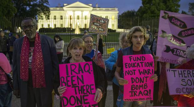 Demonstrators stand outside the White House to protest over air strikes on targets in Iraq and Syria (AP Photo/Evan Vucci)