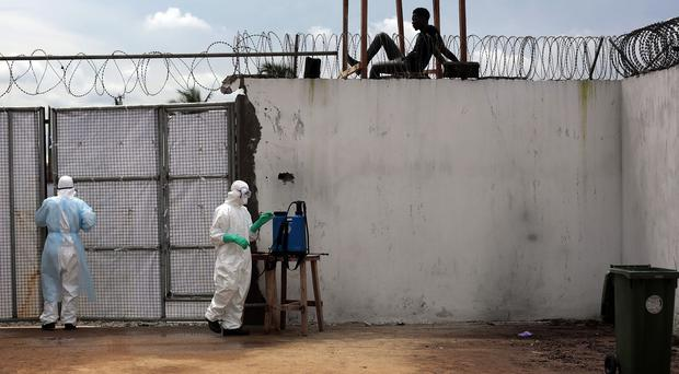 Health workers stand outside the Island Clinic Ebola isolation and treatment centre in Monrovia, Liberia (AP Photo/Jerome Delay)