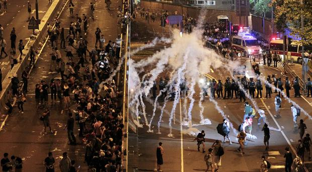 Riot police fire tear gas at student protesters occupying streets surrounding the government headquarters in Hong Kong (AP)