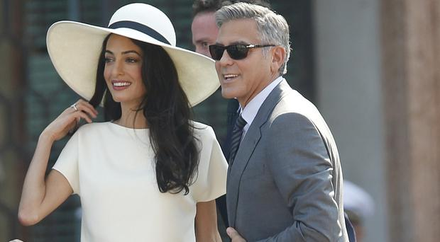 George Clooney and his wife Amal Alamuddin outside the city hall in Venice (AP)