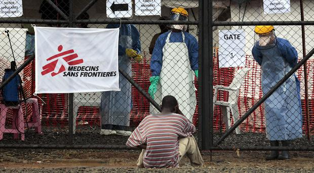 A man showing symptoms of Ebola waits to be granted entrance at a treatment centre in Monrovia, Liberia (AP)