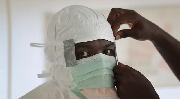 A Medecins Sans Frontieres nurse gets prepared with Personal Protection Equipment before entering a high risk Ebola zone in Monrovia, Liberia (AP)
