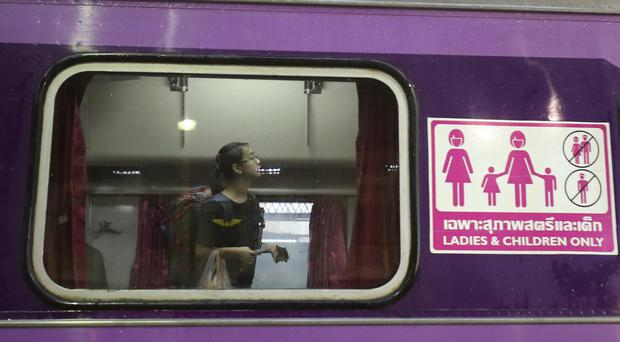 A passenger looks for her seat on a train carriage for women and children at Hua Lamphong train station in Bangkok (AP)