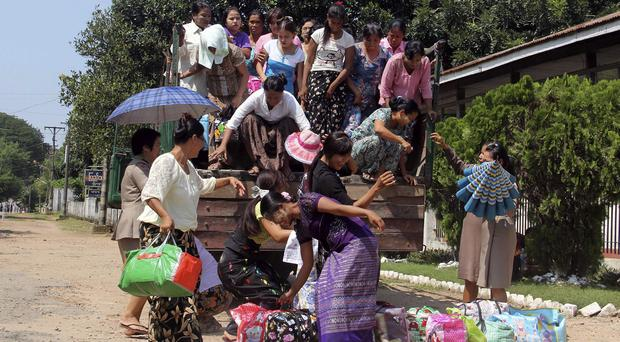 Female prisoners get off a truck after they were released from Insein prison in Yangon, Burma, after the government pardoned 3,073 inmates (AP)