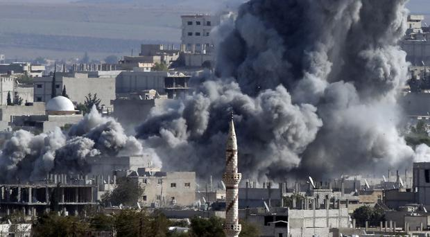 Thick smoke from an air strike by the US-led coalition rises in Kobani, Syria (AP)