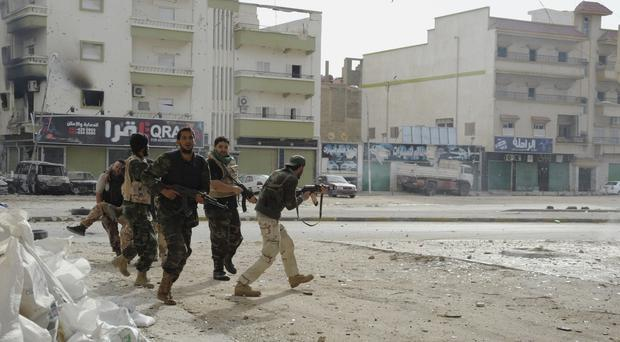 Libyan soldiers run to take cover during clashes with Islamic extremist militias in Benghazi (AP)
