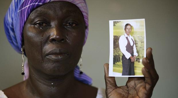 Martha Mark displays a photo of her daughter Monica Mark, who was abducted by Islamic extremists in Nigeria (AP/Sunday Alamba)