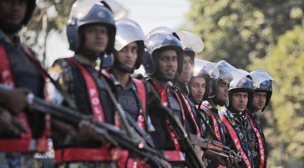 Security officers stand guard during a nationwide strike called by Jamaat-e-Islami after Motiur Rahman Nizami was sentenced to death (AP)