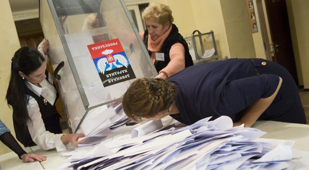 Election officials empty a ballot box during rebel elections at a polling station in the city of Donetsk (AP)