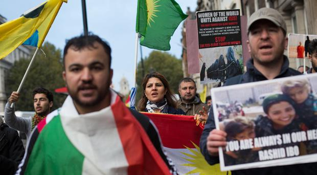 People demonstrating near Westminster Bridge in central London with Kurdish flags and banners against the IS threat to Kurdish and other minorities in Syria and Iraq