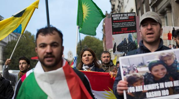 People demonstrating near Westminster Bridge in London with Kurdish flags and banners against the IS threat to Kurdish and other minorities in Syria and Iraq