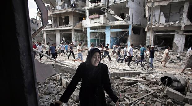 A Palestinian woman reacts after seeing her destroyed house during a 12-hour cease-fire in Gaza City's Shijaiyah neighbourhood (AP)