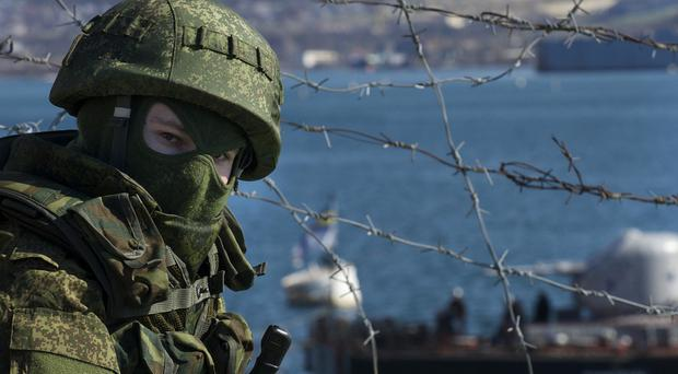 Russian soldiers guard a pier where two Ukrainian naval ships are moored, in Sevastopol, Ukraine. (AP)