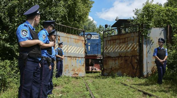 Police officers secure a refrigerated train loaded with bodies of the passengers of Malaysia Airlines Flight MH17 as it arrives in a Kharkiv factory (AP)