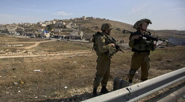 Israeli soldiers stand guard on the main road near the West bank village of Bet Sahour (AP)