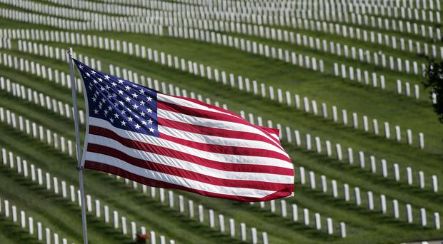 A US Flag flies over war veterans' graves at Golden Gate National Cemetery in California as the US marks Veterans Day (AP)