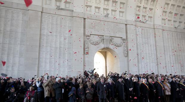 Red paper poppies fall during an Armistice Day ceremony at the Menin Gate in Ypres, Belgium (AP)