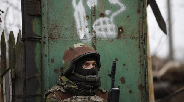 A Ukrainian volunteer fighter stands guard in a village near Donetsk in eastern Ukraine (AP)
