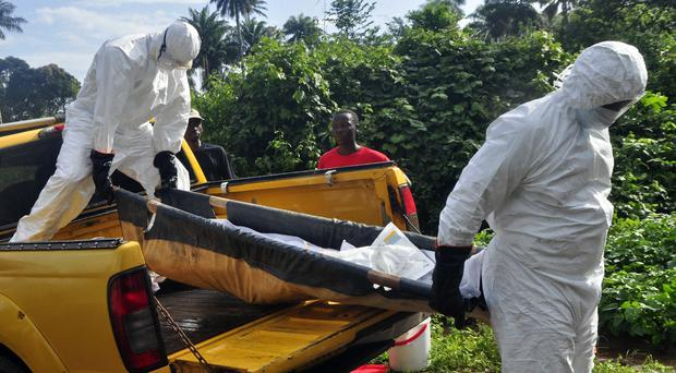 Liberian health workers carrying the body of a suspected Ebola victim (AP)