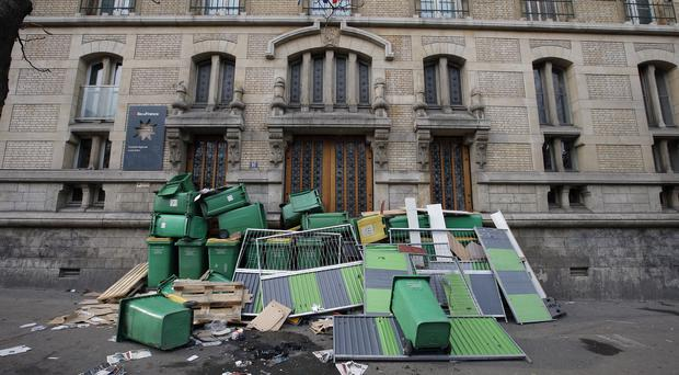 Garbage cans and barriers block the entrance to Paris Buffon high school. (AP)