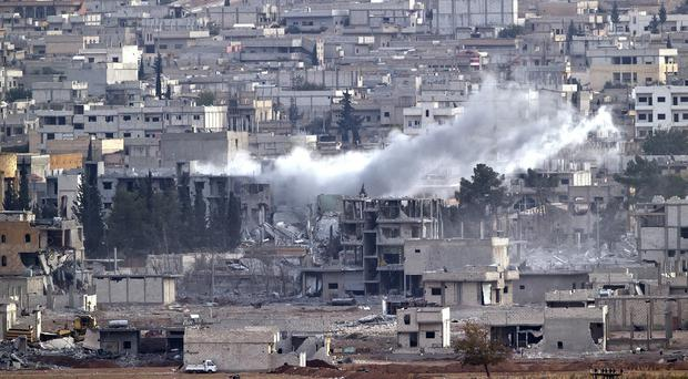 Smoke rises in the Syrian city of Kobani, seen from a hilltop outside Suruc, on the Turkey-Syria border (AP)