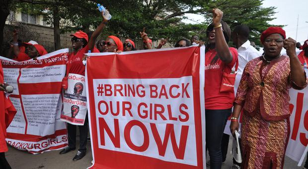 People staged a rally earlier this year calling on the Nigerian government to rescue girls taken from a school (AP)
