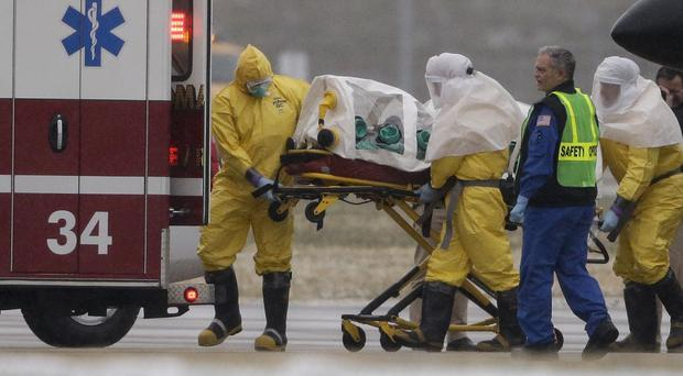 Health workers in protective suits transport Martin Salia to a waiting ambulance in Omaha. (AP)
