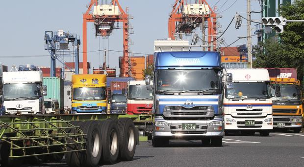 Trucks leave a container wharf in Tokyo, as Japan reported that its economy contracted in the July-September financial quarter (AP)