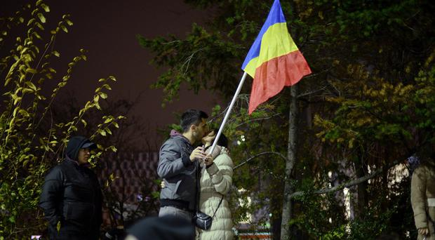 A couple kissing in Bucharest's Universitatii Square during celebrations of Klaus Iohannis's victory in the presidential run-off (AP)