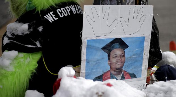 A high school graduation photo of Michael Brown rests on top of a snow-covered memorial, three months after he was shot dead by a white policeman (AP)