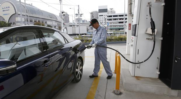 A fuel cell charge station worker 'fills' the Mirai near Toyota's Tokyo showroom (AP)