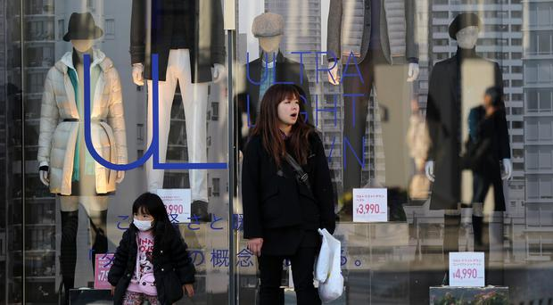 A woman and a girl stand in front of a clothing store in Tokyo amid news that Japanese Prime Minister Shinzo Abe is to delay a planned tax hike until 2017 (AP Photo/Eugene Hoshiko)