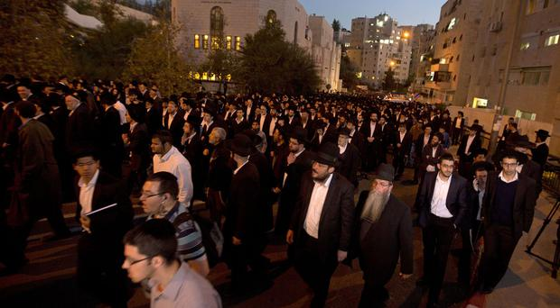 Israelis attend the funerals of Aryeh Kupinsky, Cary William Levine and Avraham Goldberg, three of the people killed in an attack on a synagogue (AP)