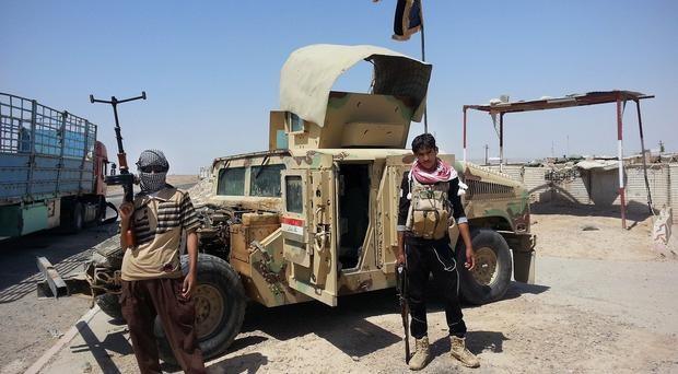 Islamic State militants stand by a captured Iraqi army Humvee at a checkpoint (AP)