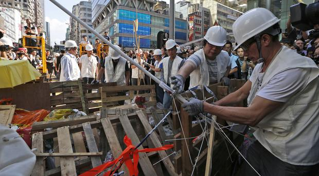 Workers start clearing away barricades at an occupied area in the Mong Kok district of Hong Kong (AP)