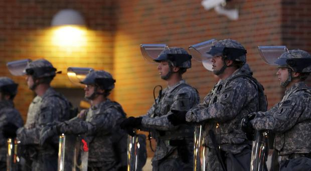 National Guard troops stand in front of the Police Department in Ferguson (AP)