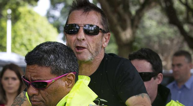 Phil Rudd jumps onto the back of his security guard after his court hearing (AP/New Zealand Herald)