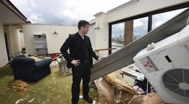 James Marriott surveys to his flat after a severe thunderstorm hit Brisbane (AP/AAP)