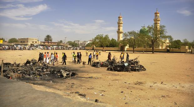People inspect the site of a bomb explosion at the central mosque in Kano, Nigeria (AP)