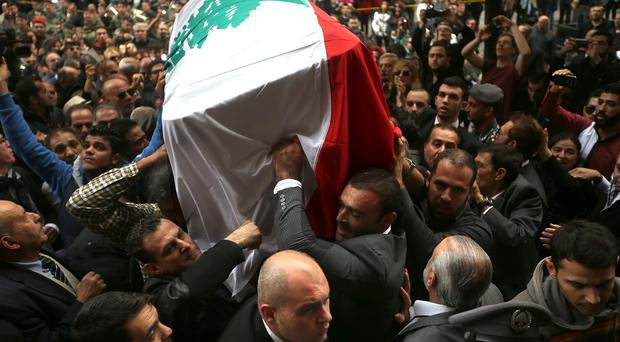 Fans of singer and actress Sabah carry her coffin wrapped with the Lebanese flag during her funeral procession outside St George Cathedral in Beirut (AP)