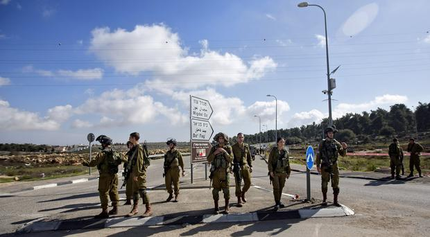 Israeli soldiers stand guard at the scene of a stabbing attack in the West Bank. (AP)