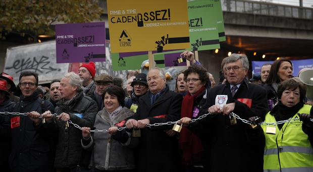 Small and medium-sized enterprise owners hold padlocks as they demonstrate in Paris. (AP)