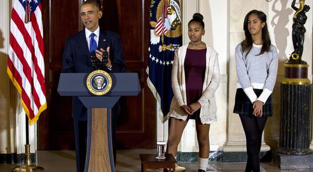 President Barack Obama, joined by his daughters Malia, right, and Sasha, centre, speaks at the White House during the presidential ceremony. (AP)