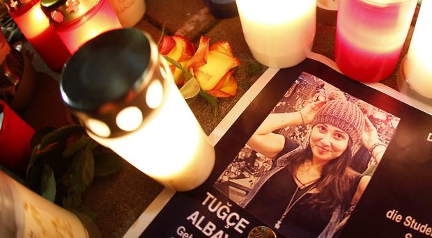 Candles are lit next to a photograph of Tugce Albayrak, in front of the hospital in Offenbach, Germany. (AP)