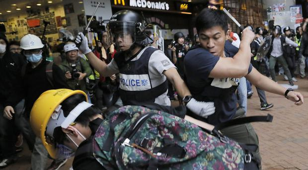 Police officers beat up protesters as they try to disperse them outside government headquarters in Hong Kong (AP Photo/Vincent Yu)