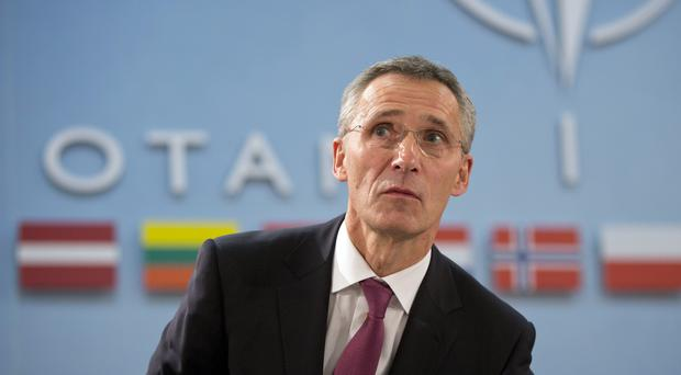 Nato secretary general Jens Stoltenberg takes his seat during a round table meeting in Brussels (AP)